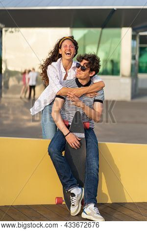 Caucasian Couple Rest After Skateboarding: Young Male And Female In Trendy Sunglasses Enjoy Summer S