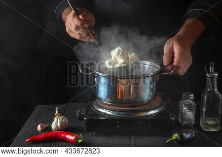 Chef Cooks Meat Dumplings In A Saucepan In The Restaurant Kitchen. Close-up Of The Hands Of The Cook