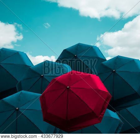 Prominent Vivid Red Umbrella Among Group Of Blue Parasol On Cloudy Blue Sky, Protection Item For Sun