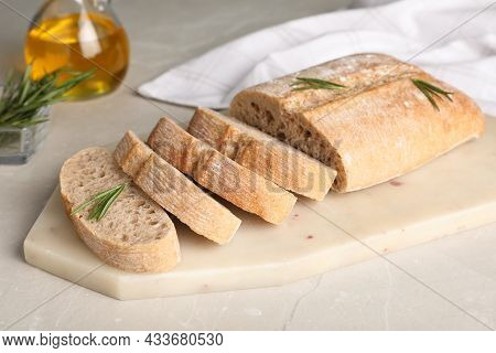 Cut Delicious Ciabatta With Rosemary On White Table