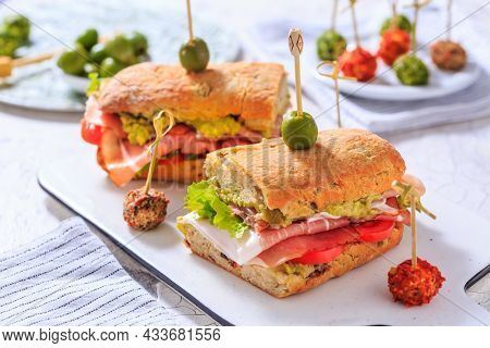 Homemade Ciabatta sandwich with guacamole, prosciutto, lettuce and tomato
