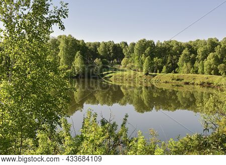 Forest Lake In Spring Surrounded By Trees, Calm Water Surface With Reflection, Bright Sunlight, Blue
