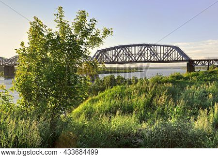 Rafters Of A Metal Bridge On High Supports, The Bank Of The Great Siberian River, Trees, Grass In Sp