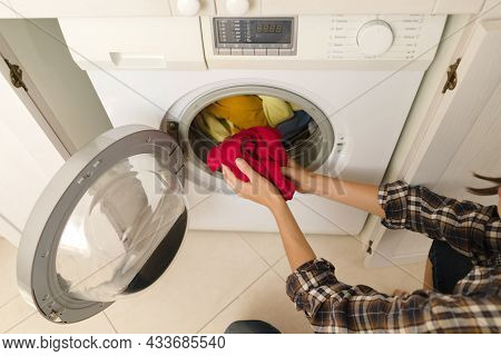 A Girl Folds Bright Clothes Into A New Washing Machine In The Bathroom At Home, A Woman Washes Thing