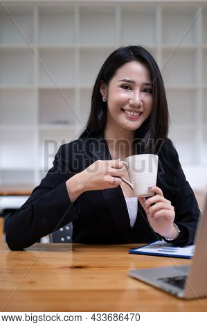 Portrait Of Cheerful Asian Woman Looking Camera And Tablet On Desk In Office. Concept Of Young Busin