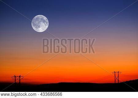 Sunset and Full Moon in sky in landscape with power lines on horion