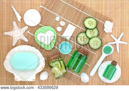 Anti ageing cucumber cosmetic beauty treatment concept with fresh slices, soap, gel and sponges. On bamboo background with decorative sea shells.