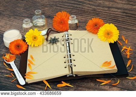 Calendula flowers used in herbal medicine with old notebook, ointment and oil bottles. Used in skincare to heal wounds, acne, eczema, stimulates collagen, is antiseptic and anti inflammatory.
