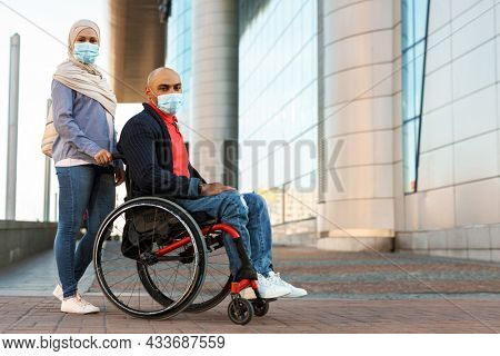 Muslim woman and disabled man wearing face mask posing outdoors