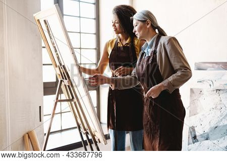 Mature teacher talking with her student during class in art school indoors