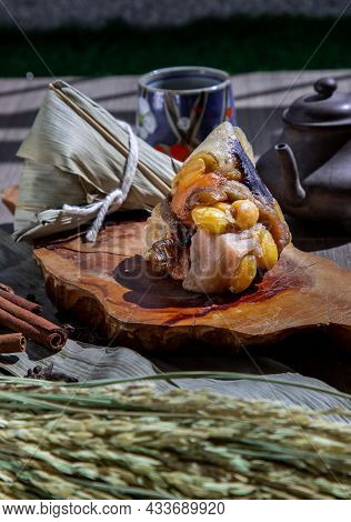Chinese Rice Dumpling (zongzi) Shaped Pyramidal Wrapped By Leaves Ingredients On Wooden Plate Served