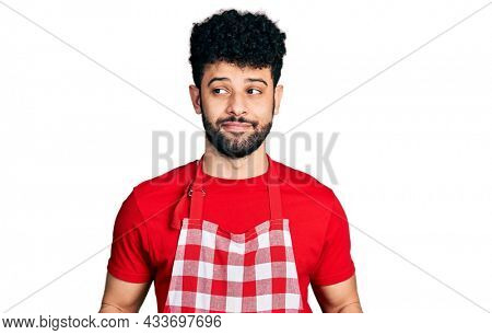 Young arab man with beard holding board with raw meat smiling looking to the side and staring away thinking.