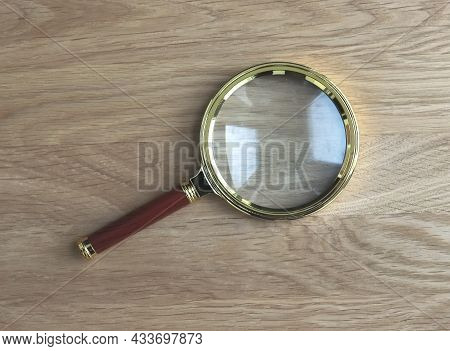 Magnifying Glass On Wooden Desk As Symbol Of Research And Study.