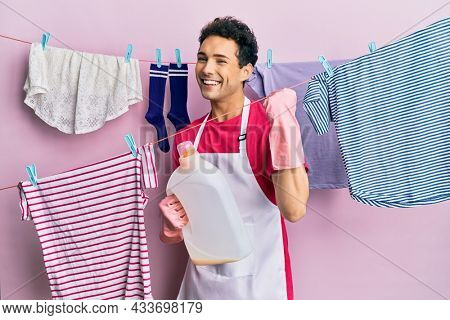 Handsome hispanic man doing laundry holding detergent bottle screaming proud, celebrating victory and success very excited with raised arms