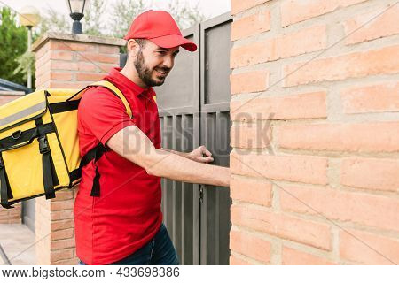 Hispanic Delivery Man In Red Uniform Ringing The Bell To Delivery Packages - Deliver Service And Sma
