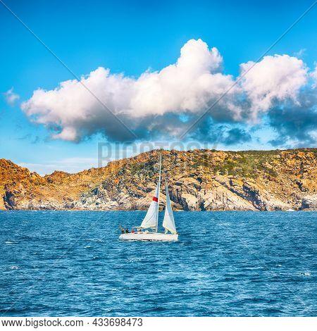 Incredible View Of Sailboat Sailing Near The Cliffs Of  Santa Teresa Gallura. Popular Travel Destina
