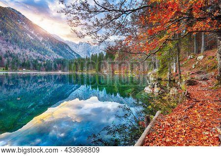 Fabulous View Of Sunset Over Fusine Lake With Mangart Peak On Background. Popular Travel Destination
