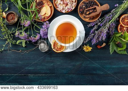 A Cup Of Tea With Dry Fruit, Flowers, And Herbs, Shot From The Top On A Dark Rustic Wooden Backgroun