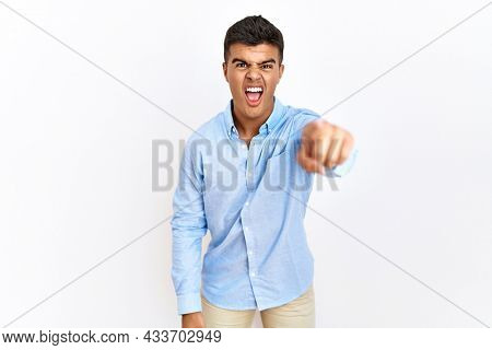 Young hispanic man wearing business shirt standing over isolated background pointing displeased and frustrated to the camera, angry and furious with you