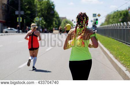 Stylish Woman Running Marathon On City Road
