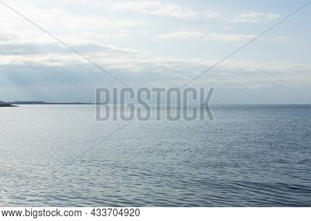 Atmospheric Seascape. Blue Clouds Bright Rays Of The Sun Illuminate The Smooth Surface Of The Sea, O