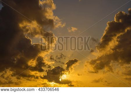 Golden Sunset Sky With Clouds And Sunrays As Background
