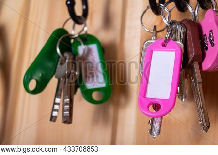 Pink Keychain With Copy Space And Keys On Hooks In Hallway. Wooden Wall As Backdrop. Many Other Keyc