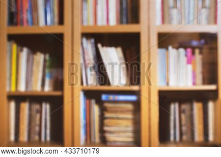 Blured Home Library Background With Colorful Books. Bookcase With Glass Doors. Stacks Of Books.
