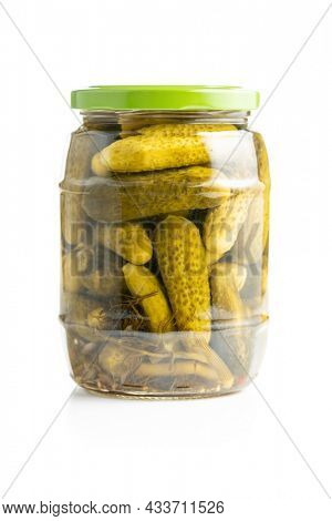 Small pickles. Marinated pickled cucumbers in jar isolated on white background.