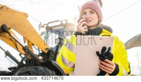 Woman with walkie talky on compost facility dispatching deliveries
