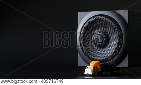 The Toy Truck Carries A Large Black Subwoofer Or Audio Speaker. Concept For A Touring Musician Or Dj