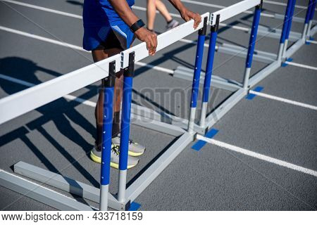 A Long Row Of Hurdles Blocks The Track And One Young African American Man Straightens Them. Track Is