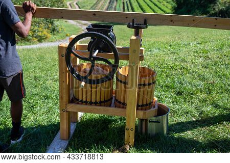 Beautiful Cider Press On A Hillside With A Farm In The Background. Young African Americna Man Turns