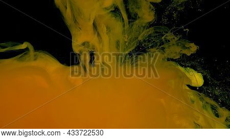 Beautiful Abstract Background. Yellow Watercolor Ink In Water On A Black Background. Waves And Drops