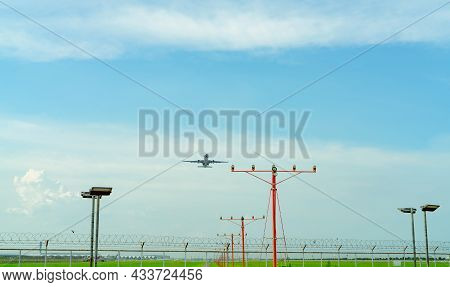 Commercial Airplane Flying Above Approach Light At The Airport. Approach Light System Concept. Airpo