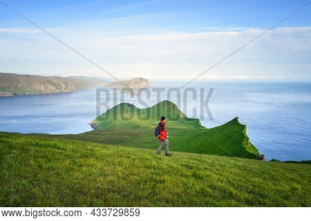 Hiking on Mykines Island, Faroe Islands. A tourist in a red jacket walks along the green hills overlooking the islands of Tindholmur and Vagar
