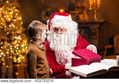 Santa Claus and little boy. Cheerful Santa is working while sitting at the table. Fireplace and Christmas Tree in the background. Christmas concept.