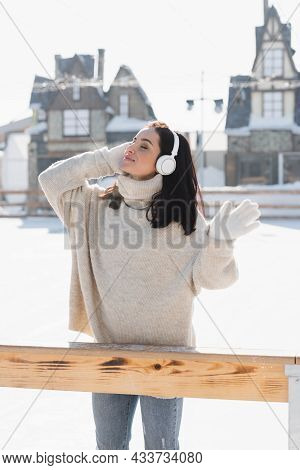 Pleased Young Woman In Wireless Headphone Listening Music On Ice Rink