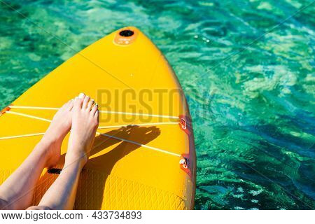 Orange Stand Up Paddle Board With Visible Legs Of A Young Girl  On The Turquoise Surface Of The Sea