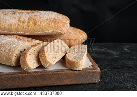 Wooden Board With Delicious Ciabattas On Black Table