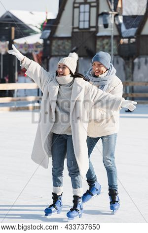 Full Length Of Happy Young Man In Winter Hat Behind Smiling Girlfriend With Outstretched Hands On Ic