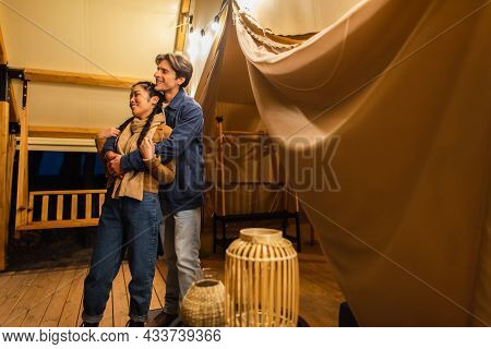 Multiethnic Couple Hugging On Terrace Of Glamping House With Light Garland