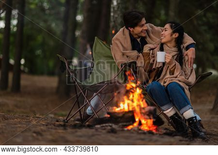 Multiethnic Couple In Blankets With Cup Taking Near Blurred Campfire