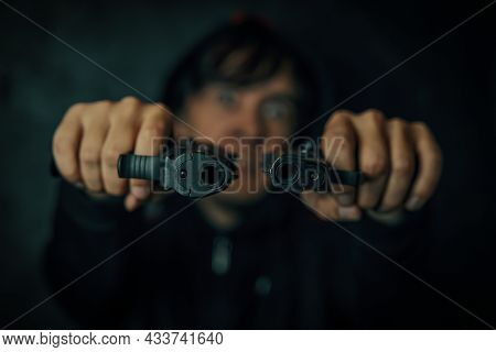 Murderer In Hood On Black Background. Guy Threatens With Firearm. Two Pistols In Mans Hands Are Poin