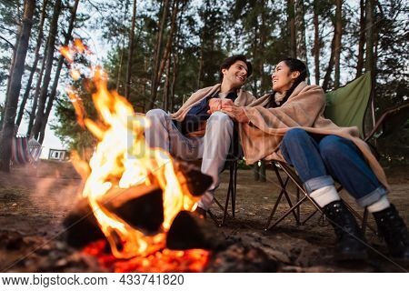 Multiethnic Couple Holding Hands Near Blurred Campfire During Weekend