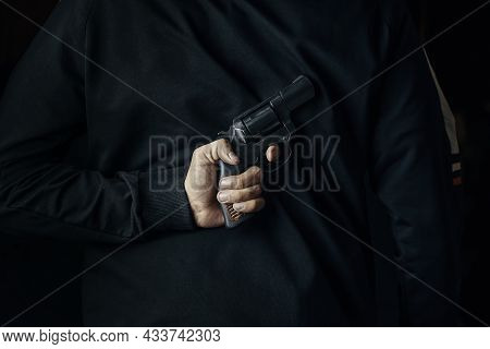 Man In Dark Clothes With Revolver On His Back. Criminal With Hand Gun. Person Holds Firearm For Atta