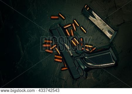 Top View Of Gun And Bullets. Flat Lay Of Pistol And Ammunition. Firearms On Dark Concrete Table. Wea