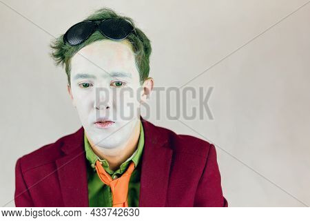 Person In Suit With Yellow Stripes Tie Looks Down. Actor With White Makeup On Face And Green Eyes An