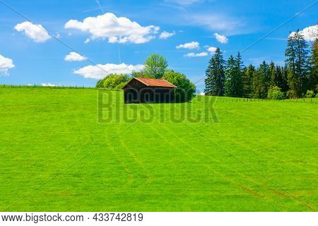 Shed On The Green Hill In The Spring . Rustic Barn On The Agricultural Field
