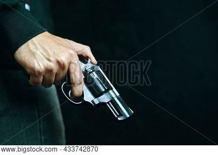 Firearm In Mans Hand. Criminal With Revolver On Dark Background. Defense Or Attack. Murderer Or Arme